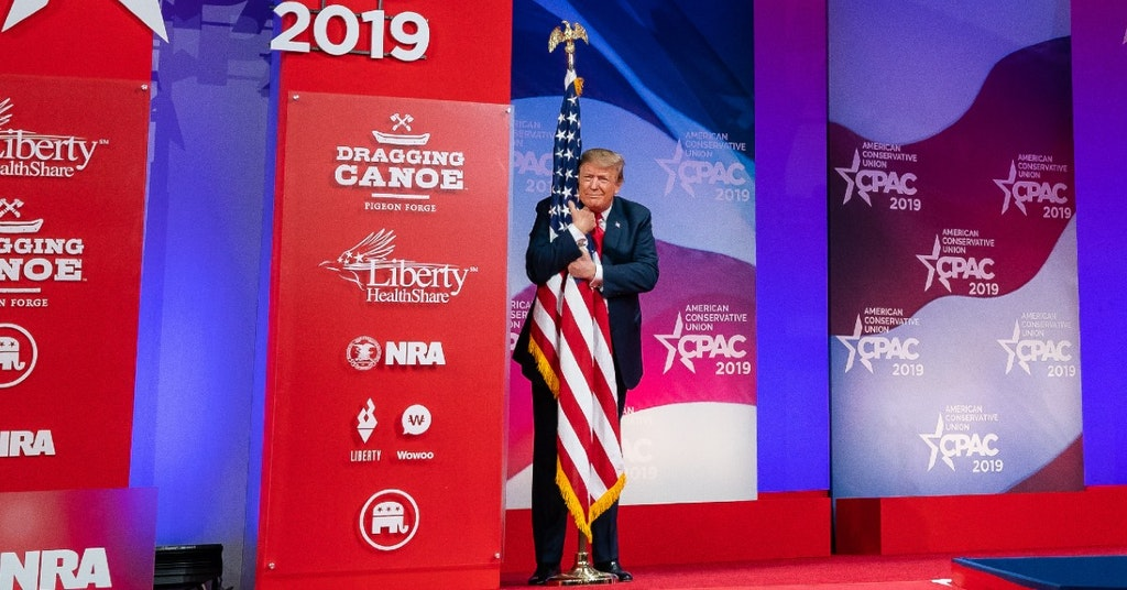 Donald Trump hugging the American flag at the 2019 CPAC