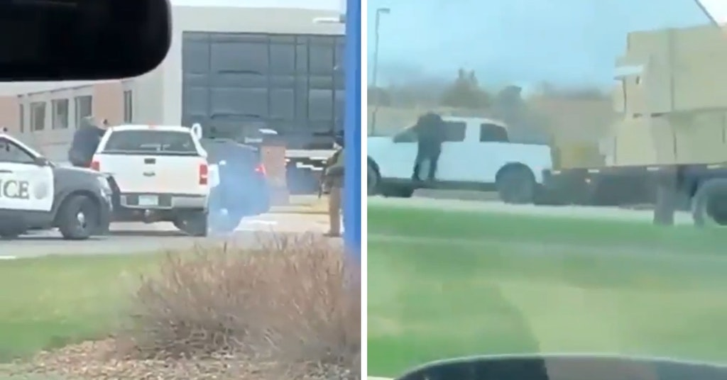 Video of a pickup truck driving away with a police officer hanging out the driver window