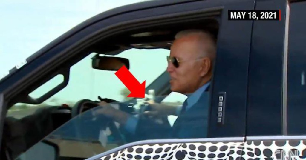 Joe Biden in the driver's seat of a pickup truck with an arrow pointing to what looks like a passenger-side steering wheel
