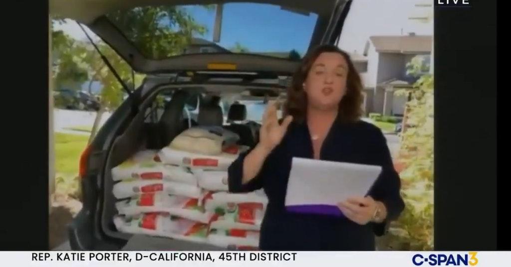 Rep. Katie Porter speaking in front of a minivan full of bags of rice
