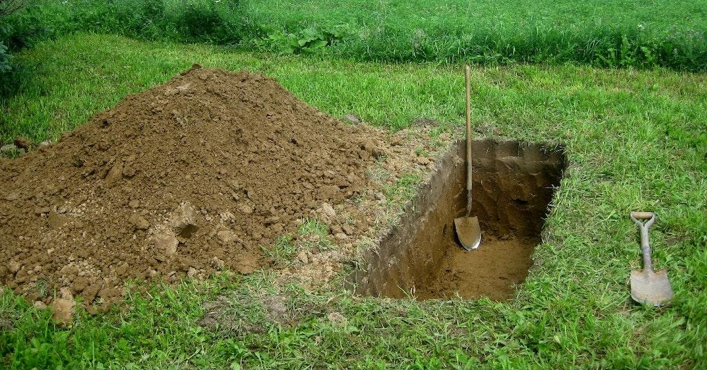 A single grave dug in a field