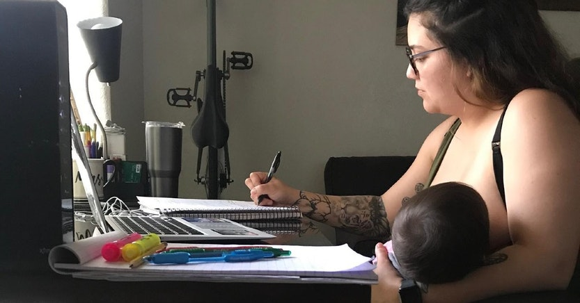 Mom breastfeeding her baby while taking notes for class